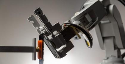 Applen Liam-robottijärjestelmä työn touhussa iPhonea purkamassa.