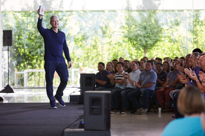 Tim Cook kädessään iPhone, jolla Apple ylitti miljardin rajan.