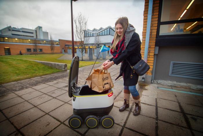 Tallinnan teknillisen yliopiston opiskelija Diana Makhova ottaa vastaan yhden historian ensimmäisistä Wolt-robottikotiinkuljetuksista