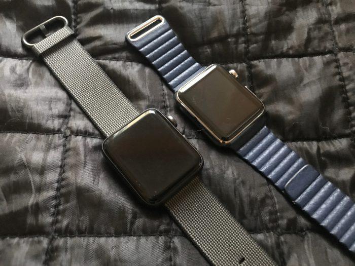 Nailonrannekkeella etualalla uusi Apple Watch Series 2 alumiiniversiona. Vieressä alkuperäinen Watch rungolla ruostumattomasta teräksestä sekä sinisellä nahkarannekkeella.