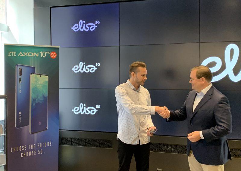 Elisan toimitusjohtaja Veli-Matti Mattila (oikealla) luovutti ensimmäisen 5G-älypuhelimen Suomessa asiakas Harri Hellströmille.
