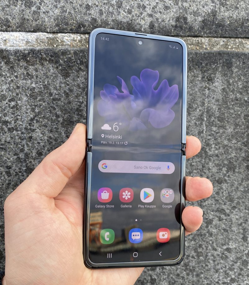 Galaxy Z Flipin näytön taitoskohta erottuu kirkkaassa valossa ja tummalla näytön sisällöllä erittäin selvästi. Reunuksen alakulmissa on kuminystyrät, jotka pehmentävät kannen sulkeutumista.