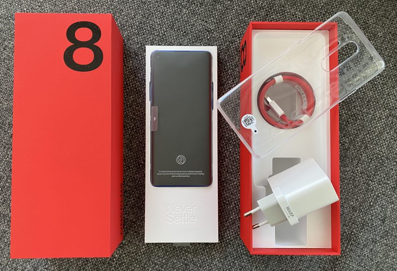 OnePlus 8 Pron myyntipakkauksen sisältö: itse puhelin, läpinäkyvä suojakuori, kaapeli ja Warp Charge 30T -pikalaturi.