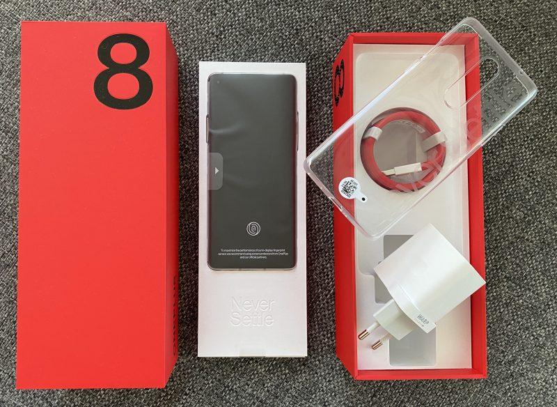 OnePlus 8:n myyntipakkauksen sisältö: itse puhelin, läpinäkyvä suojakuori, kaapeli ja Warp Charge 30T -pikalaturi.