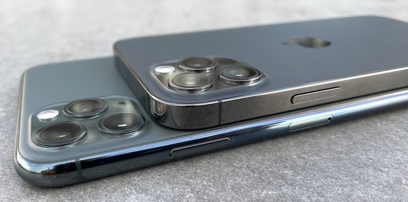 Päällä iPhone 12 Pro, alla iPhone 11 Pro Max. Kyljet ovat muuttuneet pyöristetyistä tasaisiksi.