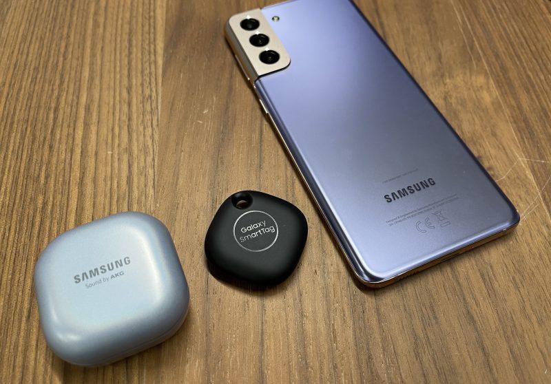 Keskellä Galaxy SmartTag. Kokoverrokkeina Galaxy Buds Pro -latauskotelo ja Galaxy S21+.