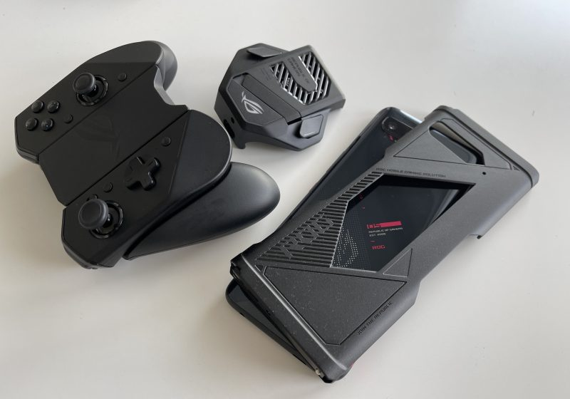 Kuvassa ROG Kunai 3 GamePad koottuna irrallisen peliohjaimen muotoon, AeroActive Cooler 5 -tuuletin sekä ROG Phone 5:n päällä peliohjaimen puoliskojen liittämiseksi kiinni puhelimeen tarvittava sovitinosa.