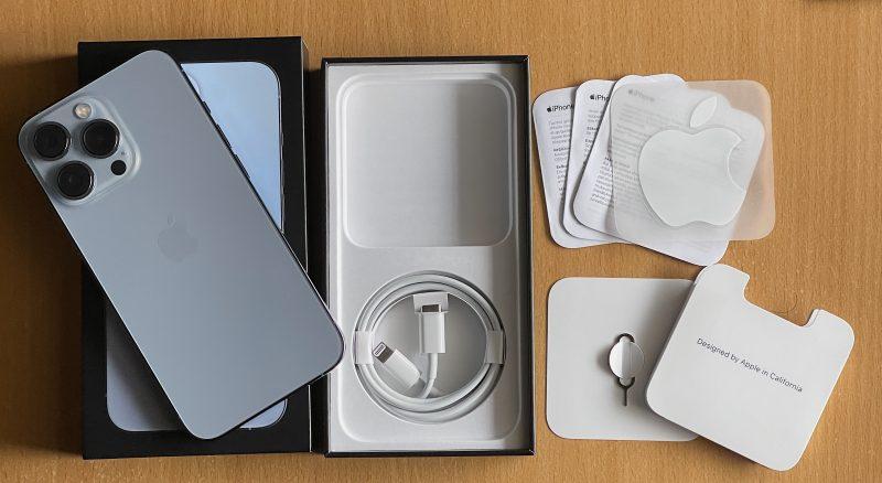 iPhone 13 -myyntipakkauksissa on itse puhelimen lisäksi vain USB-C-Lightning-kaapeli, lappusia ja Apple-tarra sekä SIM-korttikelkan avaustyökalu. Tässä esimerkkinä iPhone 13 Pro.